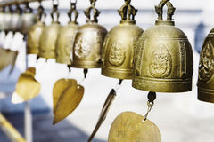 Many golden buddhist bells with wishes in sunlight Stock Photos