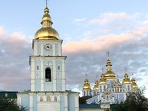 Many golden domes of churches. Against the background of beautiful pink clouds stock image