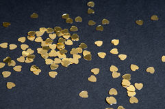 Many golden heart sparkles on black background Royalty Free Stock Images