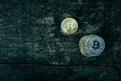 Many golden and silver bitcoins on a wooden surface, background with vintage effect, cryptocurrency concept for business idea, clo. Many golden and silver royalty free stock images