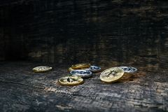 Many golden and silver bitcoins on a wooden surface, background with vintage effect, cryptocurrency concept for business idea, clo. Many golden and silver stock photos