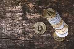Many golden and silver bitcoins on a wooden surface, background with vintage effect, cryptocurrency concept for business idea, clo. Many golden and silver stock image