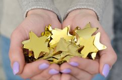Many foil stars in hand. Many golden stars of foil in the hands of a girl. The atmosphere in the photo conveys the Christmas mood royalty free stock photo
