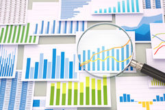 Many graphs and magnifying glass. Stock Image