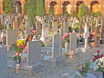 Many gravestones and tombs in the cemetery with many flowers Stock Photos