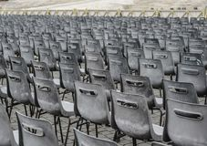 Many gray chairs in straight lines on a square royalty free stock image