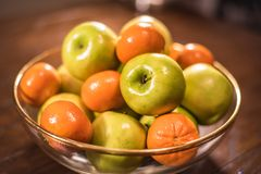 Green apples and oranges in clear bowl on table Royalty Free Stock Image