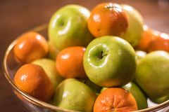Green apples and oranges in clear bowl on table Royalty Free Stock Photo