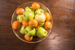 Green apples and oranges in clear bowl on table Stock Images
