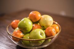 Green apples and oranges in clear bowl on table Royalty Free Stock Photos