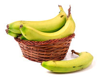 Many green bananas in brown wicker basket isolated on white Stock Photography