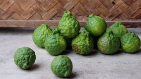 Many of Green Bergamot. The green bergamot on wooden table and bamboo background royalty free stock image