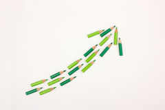Many green pens forming an arrow pointing upwards Stock Photo