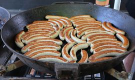 Many grilled sausages, austrian bratwursts , in a large black pan in a street food shop.  stock photo