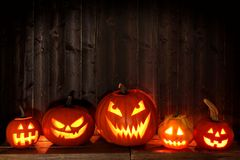 Many Halloween Jack o Lanterns at night against dark wood. Group of Halloween Jack o Lanterns at night with a rustic dark wooden background Royalty Free Stock Photo