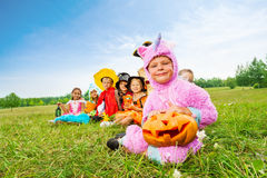 Many Halloween kids wear costumes sit in long row Stock Images