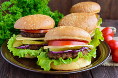 Many hamburgers at home (bun, tomato, cucumber, onion rings, lettuce, pork chops, cheese). In a clay bowl on a wooden background. Close-up Royalty Free Stock Image