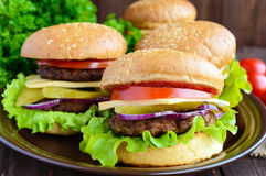 Many hamburgers at home (bun, tomato, cucumber, onion rings, lettuce, pork chops, cheese). In a clay bowl on a wooden background. Close-up Royalty Free Stock Photography