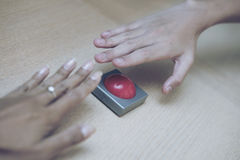 Many hand grab for the red button on wood table. Stock Photos