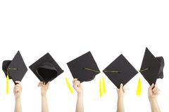 Many hand holding graduation hats. And isolated on white stock images