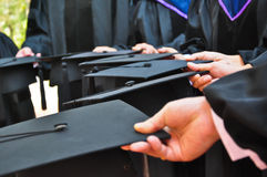 Many hand holding graduation hats, close up Royalty Free Stock Images
