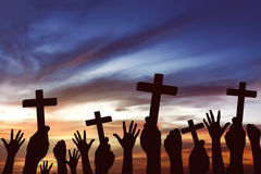 Many hand pray and holding christian cross. Over sunset background Royalty Free Stock Photography