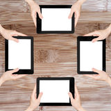 Many hand in the tablet PC in wooden table. Stock Photography