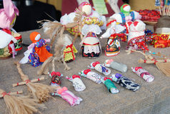 Many handmade dolls on the table. Many small handmade colorful dolls made of fabric and straws. They do not have faces due to old paganism traditions. Souvenirs Royalty Free Stock Images