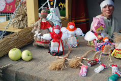 Many handmade dolls on the table. Many handmade colorful dolls made of fabric and straws. They do not have faces due to old paganism traditions. Souvenirs. A Royalty Free Stock Image