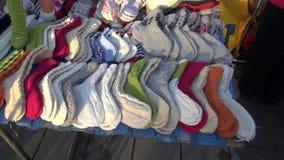 Many handmade knitted socks in  market stock video