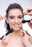 Many hands applying make up stock photography