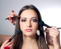 Many hands applying make up. Simple background royalty free stock photo