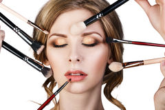 Many hands applying make-up to glamour woman. Stock Image