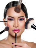 Many hands applying make up on a woman Royalty Free Stock Photo