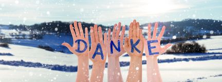 Many Hands Building Danke Means Thank You, Winter Scenery As Background stock photo