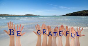 Many Hands Building Word Be Grateful, Beach And Ocean. Many Hands Building English Word Be Grateful. Beautiful Beach, Ocean And Sea As Background stock photography