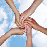 Many hands connecting for help. In a spiral under a sky royalty free stock photos