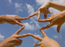 Many hands connecting to star. Shape under sky royalty free stock images