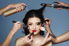 Many hands with cosmetics brush, shadows doing make up Royalty Free Stock Photo