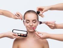 Many hands doing makeup isolated on white. Many hands of visage artists doing makeup isolated on white background stock image