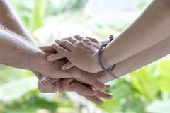 Many hands getting together in the center of a circle. Close up outdoor shot. Arm stacked together one by one in unity and teamwork. Many hands getting together royalty free stock photography