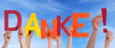 Many Hands Holding a Colorful Danke. Many Hands Holding the German Word Danke Which Means Thanks in Front of the Sky stock photo
