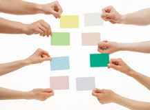Many hands holding colorful paper cards Stock Photography
