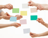 Many hands holding colorful paper cards. On white background royalty free stock photos
