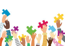 Many hands holding colorful puzzle pieces Stock Photography