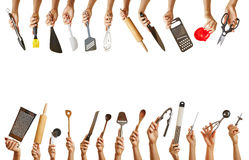 Many hands holding different kitchen tools. Frame with many hands holding different kitchen tools like knife, scissors and spoon Royalty Free Stock Image