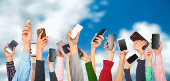 Many hands holding mobile phones against. The blue sky Royalty Free Stock Image
