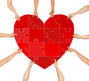 Many hands holding puzzle heart isolated. On a white background royalty free stock images