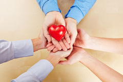 Many hands holding a red heart. Many hands holding together a little red heart royalty free stock photography