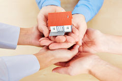 Many hands holding a small house. Many hands holding together a small house as concept for security and protection stock photos